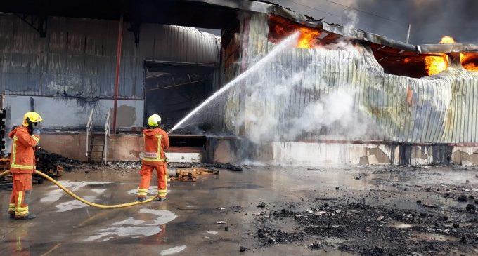 Un total de 16 bombers continuen treballant en l'incendi en una nau del polígon de la Cova