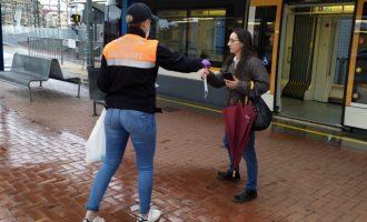 Efectius de la Policia i membres de Protecció Civil reparteixen mascaretes en els accessos al transport públic de Burjassot